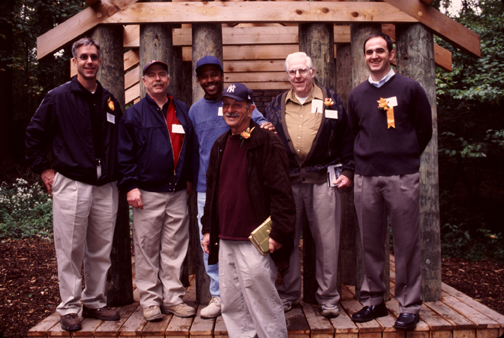 Artist Ed Levine (center) in front of Thoreau's Hut with (left to right) George Schmidt, Jr., Mark Boston, and Ray Haynes of the installation team, George Schmidt, Sr. and Art Association Program Manager Charles Moleski.