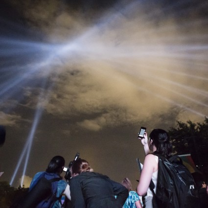 "Participants in ""OPEN AIR"" by Rafael Lozano-Hemmer look up at the searchlights"