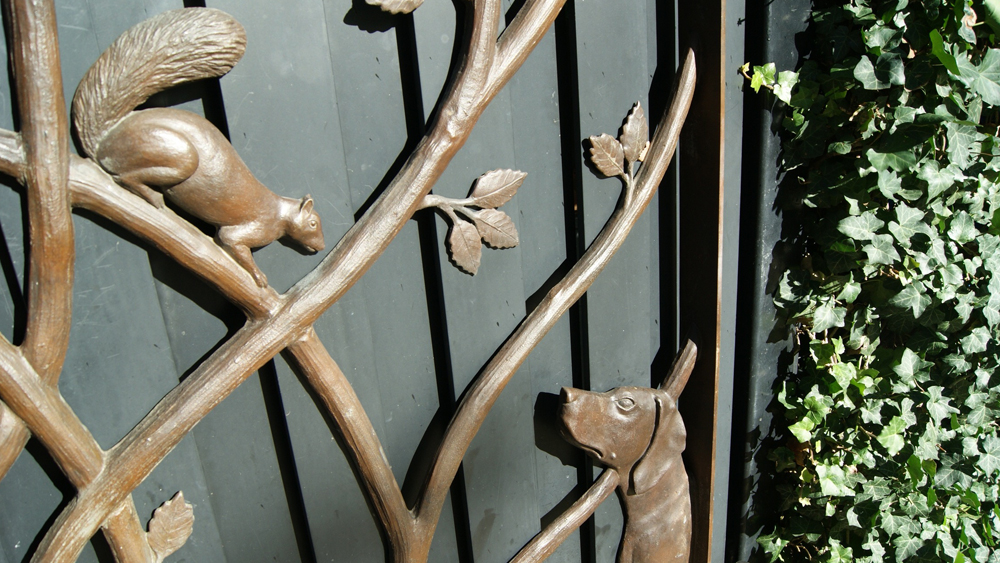 A detail of a squirrel and a dog on the Gardener's Cottage Gates