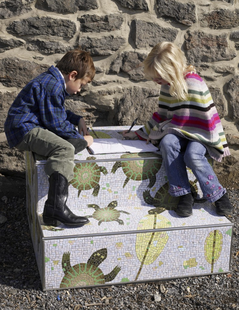 "Children sit atop one of the stoops of ""Manayunk Stoops"" by artist Diane Pieri"